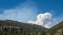 smoke from a wildfire coming from behind a mountain