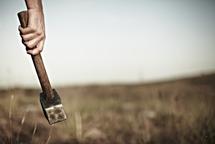 Man holding hammer in field