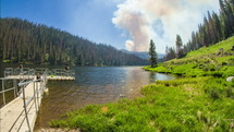 Timelapse of wildfire smoke movement over a lake with a busy pier, surrounded by mountains and trees.