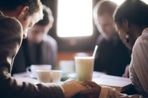 a group holding hands in prayer at a Bible study