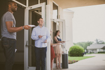 greeters handing out church bulletins at a church entrance