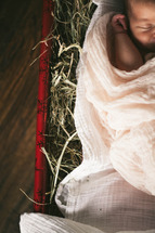 baby lying in a Christmas present full of hay - baby Jesus