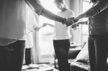 Women holding hands in a prayer circle during a bible study.